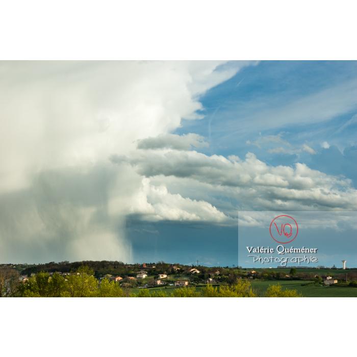 Vue de loin d'un cumulonimbus déchargeant la pluie dans un ciel bleu - Réf : VQ_CIEL-136 (Q1)