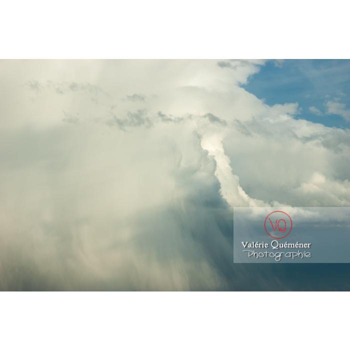 Vue de loin d'un cumulonimbus déchargeant la pluie dans un ciel bleu - Réf : VQ_CIEL-141 (Q1)