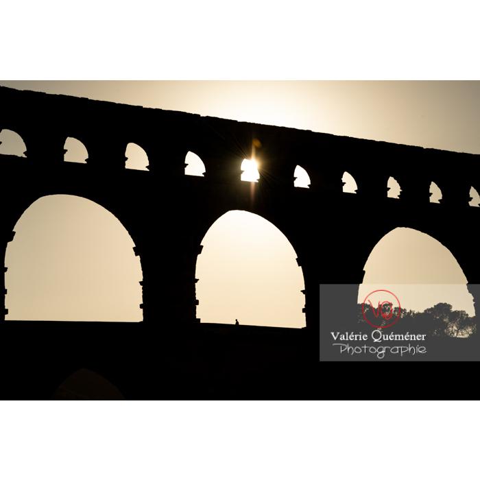 Soleil à travers une arche du pont du Gard (MH) au coucher du soleil / Occitanie - Réf : VQFR30-0436 (Q3)
