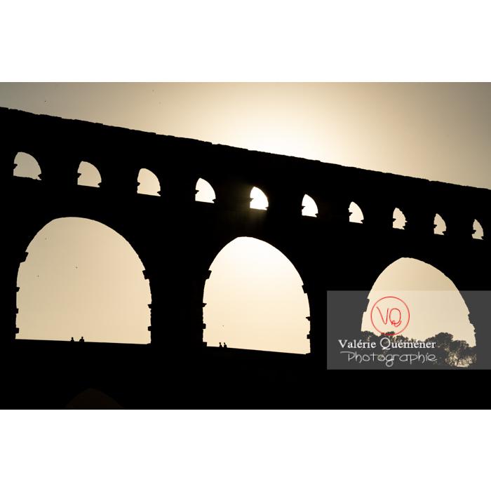 Silhouette des arches des niveaux supérieurs du pont du Gard (MH) au coucher du soleil / Occitanie - Réf : VQFR30-0439 (Q3)