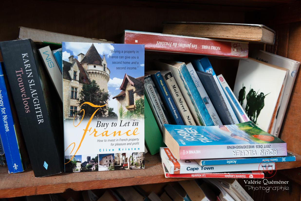 Livres anglais dans la bibliothèque de rue du village de Trémolat dont un livre expliquant aux anglais comment acheter une propriété en France | © Valérie Quéméner - Réf : VQFR24-0279